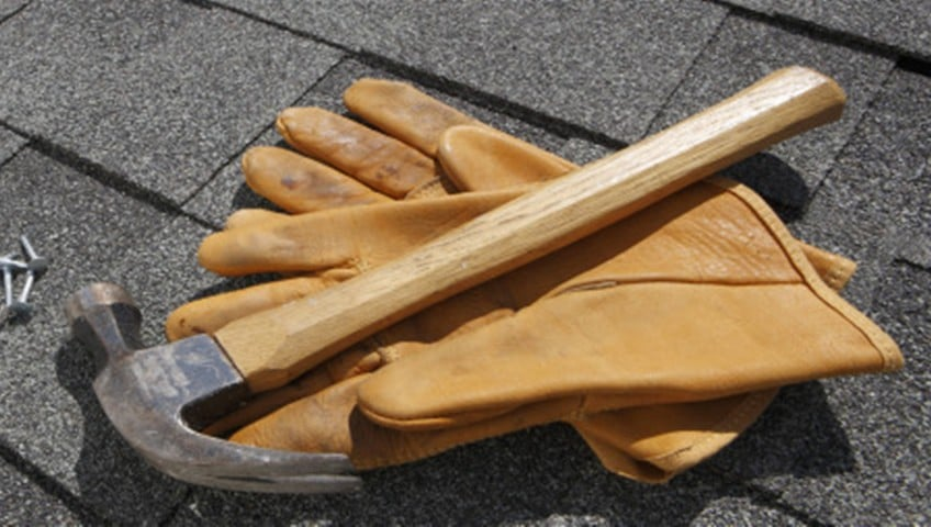 A hammer and gloves lying on a roof