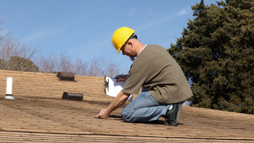 A home inspector checking the roof of a house