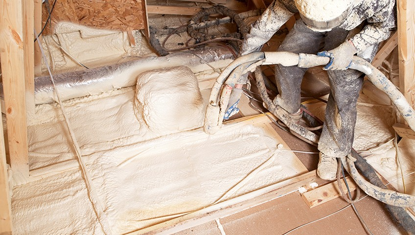 A worker doing foam insulation in the attic of a house