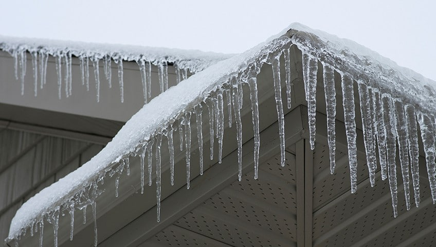 Frozen gutters and icicles on roof edges