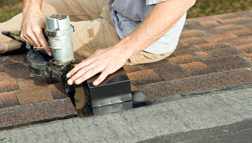 A workman nailing a bathroom vent to the roof